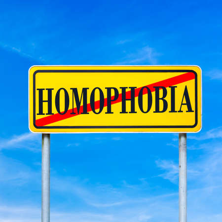 homophobia: Homophobia written on yellow street sign and crossed off. Stop homophobia concept.