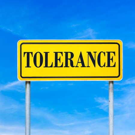 tolerancia: Tolerancia palabra escrita en la muestra de calle amarilla. Más de cielo azul. Foto de archivo
