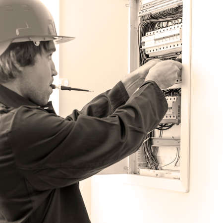 fusebox: Electrician checking fuse box. Stock Photo