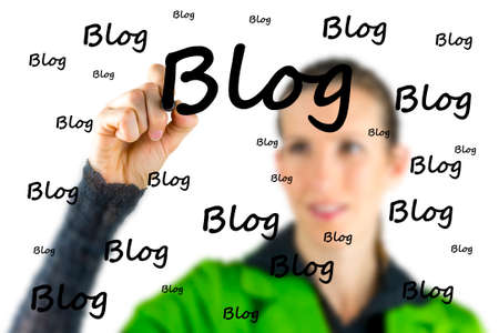 blogger: Female blogger writing the word Blog on a virtual interface with a marker pen as she extols the importance of communication and networking with the social community via a blog or diary Stock Photo