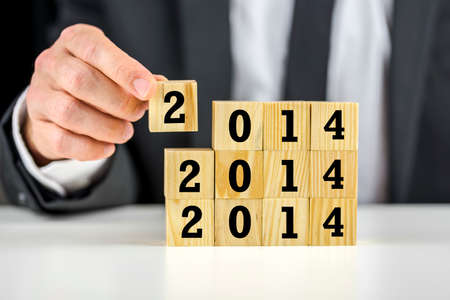 forthcoming: Businessman with 2014 New Year building blocks carefully stacking them on top of each other depicting business planning, strategy and development in the forthcoming year
