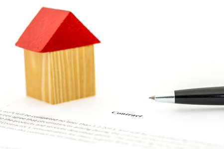 selling house: Concept depicting the buying or selling of a house with a ballpoint pen and wooden model of a home standing on a written contract which could be either a deed of sale, lease or insurance agreement Stock Photo