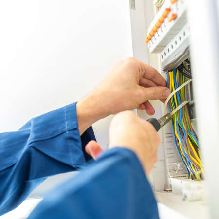 Electrician installing an electrical fuse box in a house working with pliers on the wiring circuits