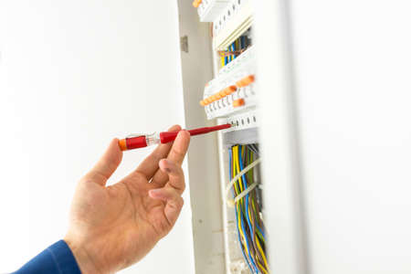 Electrician testing an electrical circuit board with a handheld tester to determine if there is current and voltage during repairs or installation of a domestic supply