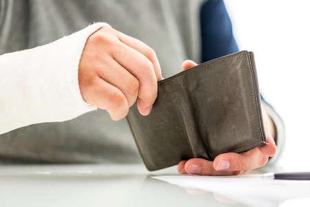 석고에서 그의 팔을 가진 남자는 병원이나 의사 비용과 응급 의료 치료 비용의 개념 돈을 제거 지갑 들고 캐스팅