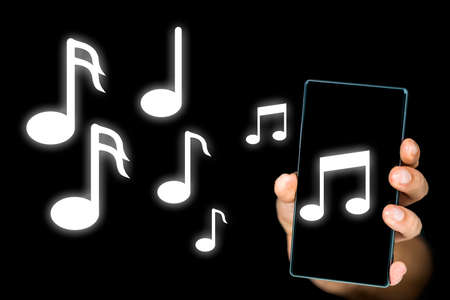 audible: Conceptual image of music notes issuing from an mp3 music player or notes depicting an audible musical ringtone on a mobile phone