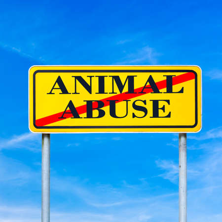 Conceptual image of a bright yellow traffic sign against a blue sky with the words - animal abuse - crossed through depicting stopping harm to animals in laboratories and at the hands of people Stock Photo