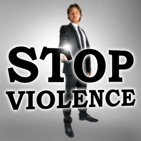 banish: Man standing behind a large, transparent sign or slogan with the words, Stop violence.