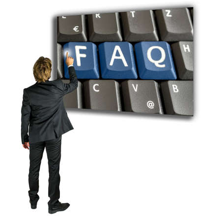 activating: Businessman standing activating a FAQ key on a computer keyboard as he seeks further information and a solution to his problem or query online over the internet