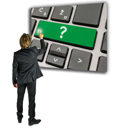 seeks: Businessman with a query or problem standing activating a Question mark on a computer keypad as he seeks online help and support