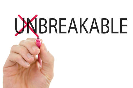 breakable: Conceptual image with the word Unbreakable on a virtual electronic screen or interface with the Un crossed out by a man holding a pen depicting two opposing characteristics of breakable vs unbreakable