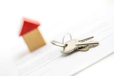 equidad: Manojo de llaves de la casa se extiende sobre una mesa en frente de un pequeño modelo de madera de una casa conceptual del logro, la propiedad y la seguridad de un patrimonio mobiliario o inmobiliario