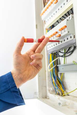 Elektriker Überprüfung der Verkabelung der Stromversorgung eines Hausfeld Haus, wie er führt Reparaturen, Wartung, während der Installation oder während einer Inspektion für eine Compliance-Zertifikat