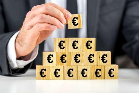 equidad: Hombre que al edificar una pirámide de los símbolos del euro en los bloques de construcción de madera que hace la última cubo en la parte superior, conceptual del éxito empresarial y del crecimiento o de la situación económica mundial en la CEE