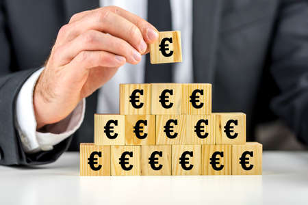 eec: Man building a pyramid of euro symbols on wooden building blocks placing the last cube on the top, conceptual of business success and growth or of the global economic situation within the EEC Stock Photo
