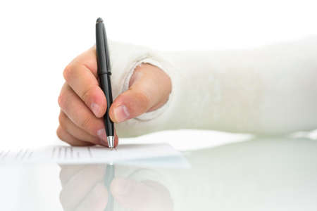 plaster of paris: Man with his arm and wrist in a plaster cast from a fracture injury or surgery struggling while writing a note with a ball point pen, closeup of his hand