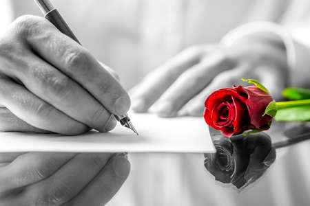Close up of the hands of a man writing a love letter to his sweetheart with a single romantic red rose with selective colour lying on the desk alongside him Standard-Bild