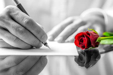 Close-up van de handen van een man schrijven van een liefdesbrief aan zijn liefje met een romantische rode roos met selectieve kleur, liggend op het bureau naast hem