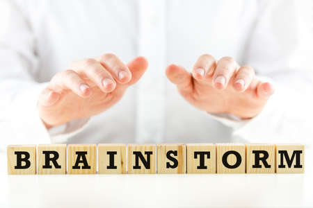 shirtsleeves: Conceptual image of a businessman in shirtsleeves holding his hands protectively above a line of wooden cubes with the word - Brainstorm - closeup view Stock Photo