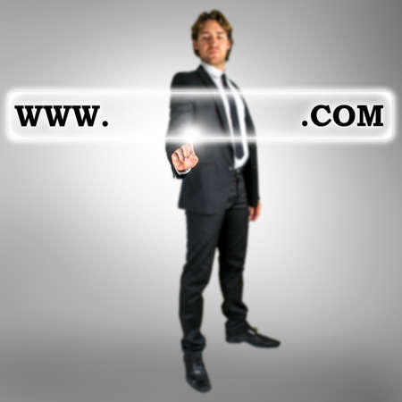 domain: Businessman activating a web address with words www and dot com with copyspace between in a navigation bar on a virtual interface or screen with his finger from behind