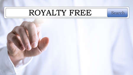 Close-up of a hand pressing with the finger on the words royalty free written in the search bar of a virtual screen, with copy space Stock Photo