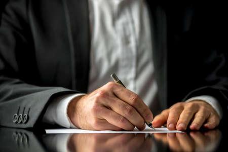firmando: Imagen conceptual de un hombre que firma un documento última voluntad y testamento. Foto de archivo