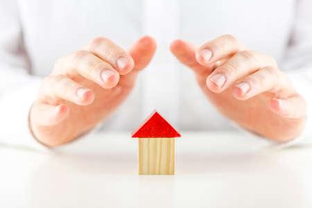 curare teneramente: Maschio mani che coprono e proteggono un piccolo modello di legno di una casa o casa concettuale di proprietà, la sicurezza, l'assicurazione e la sicurezza