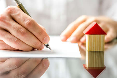 Conceptueel beeld van een man ondertekening van een hypotheek of verzekering of de akte van verkoop bij het kopen van een nieuw huis of de verkoop van zijn bestaande met een kleine houten model van een huis naast