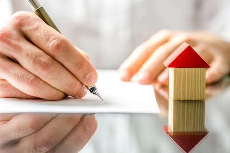 equidad: Imagen conceptual de un hombre que firma una hipoteca o contrato de seguro o de la escritura de compraventa en la compra de una nueva casa o la venta de su ya existente con un pequeño modelo de madera de una casa al lado