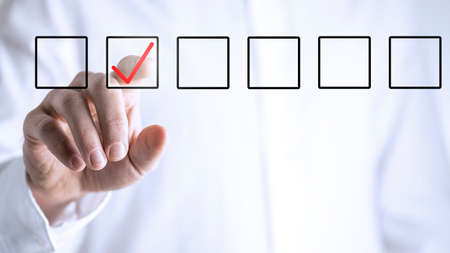 Man ticking a check box in a line of empty boxes on a virtual screen or interface with his finger Stock Photo