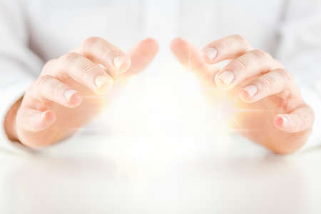soothsayer: Hombre con una bola de cristal brillante sosteniendo sus manos de manera protectora por encima de ella para sentir la energ�a como lo predice o predice el futuro conceptual de un adivino, adivino, m�stico o clarividente
