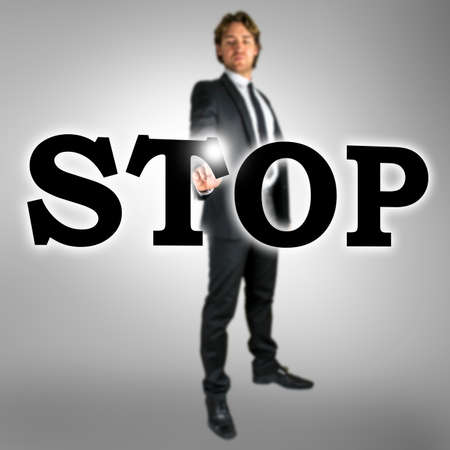 activating: Stop written in large black capital letters on a virtual interface with a stylish businessman in a suit standing behind activating the touchscreen with a finger, conceptual image on a grey background