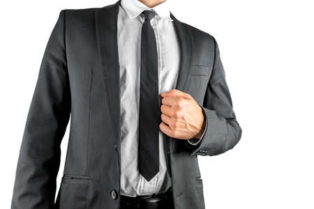 unbuttoned: Torso of a businessman in a stylish suit with the jacket unbuttoned confidently holding his lapel with his hand isolated on white Stock Photo