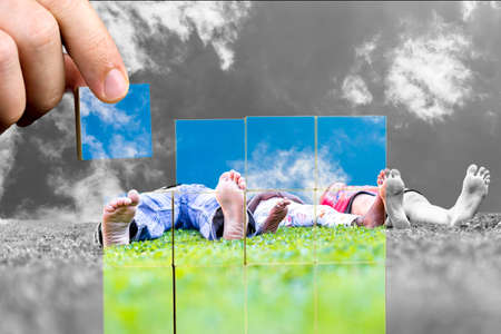 Wish for a happy family with a low angle of image of barefoot people lying on green grass with the hand of a man replacing the background black and white image with colour photo