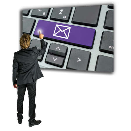 enlarged: Businessman sending an email message standing in front of an enlarged computer keyboard with an email icon on one key as he makes an online connection to contact a website or person over the internet Stock Photo