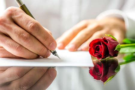carta de amor: Primer plano de las manos de un hombre rom�ntico escribiendo una carta de amor a su novia para el d�a de San Valent�n Foto de archivo