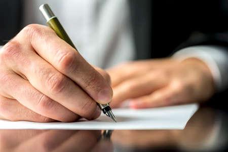 Gros plan des mains d'un homme d'affaires dans une signature de costume ou la rédaction d'un document sur une feuille de papier blanc