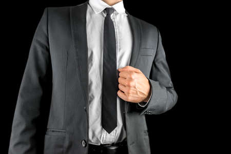 self assurance: Close up of the torso of a confident businessman in a suit holding the lapel of his stylish jacket in his hand conceptual of success and self-assurance