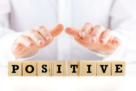 favourable: Man holding his hands protectively over the word Positive on a row of wooden cubes  Stock Photo