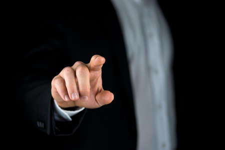 activating: Man in a suit reaching out and touching a blank virtual interface with his finger