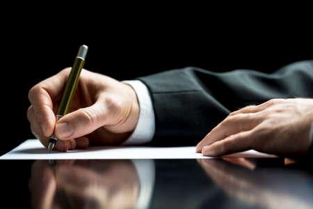 signing: Uomo d'affari scrivere una lettera, note o corrispondenza o la firma di un documento o di un accordo, vista da vicino della sua mano e la carta