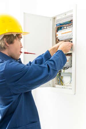 Zijaanzicht van elektricien in gele harde hoed en blauwe overalls repareren zekeringenkast, witte achtergrond.