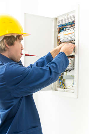 fuse box: Side view of electrician in yellow hard hat and blue overalls repairing fuse box, white background. Stock Photo