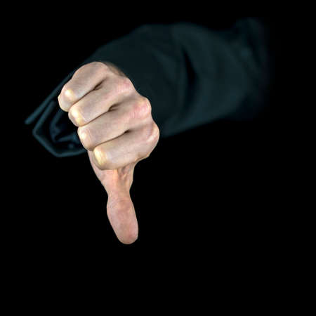 negativity: Close-up of a hand with black sleeve showing the thumb down, gesture of disapproval, isolated on black background