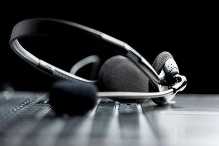 헤드셋은 온라인 커뮤니케이션 또는 콜 센터, 낮은 각도보기의 개념 노트북 컴퓨터 키보드에 누워 스톡 콘텐츠