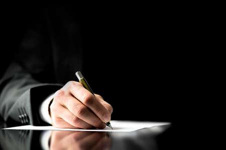 levelezés: Üzletember aláírása egy dokumentumot, jegyzeteket, kiegészítve egy kérdőívet, vagy írásban levelezés, közelről véve a kezét, és a papír