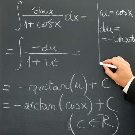 Hand of a businessman writing scientific formula on a blackboard conceptual of a presentation, research, learning or development photo