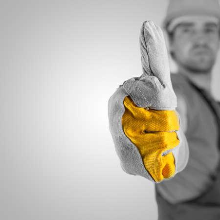 Bouwvakker of bouwer in een beschermende helm en handschoenen geven een duim omhoog gebaar van goedkeuring en succes met selectieve focus op zijn gehandschoende hand