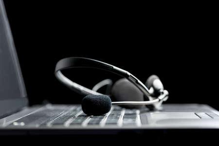 hands free: Bajo el �ngulo de vista de cerca de un auricular miente en el teclado de una comunicaci�n libre de un ordenador port�til abierto conceptual de las manos Foto de archivo