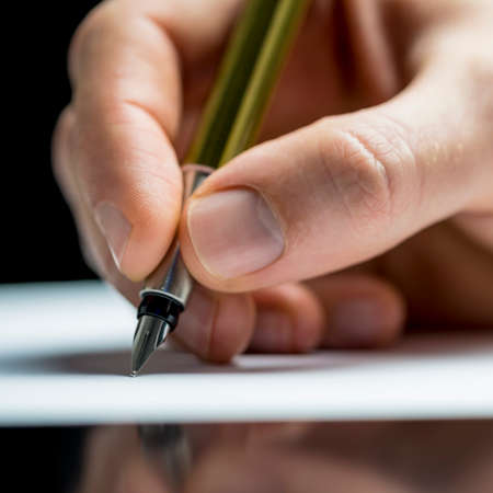fountain pen writing: Close up of the hand of a man writing a letter or notes with a fountain pen on a sheet of paper or signing a document or contract